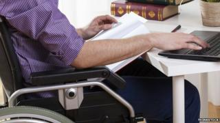 a man in a wheelchair sitting at a desk with a laptop