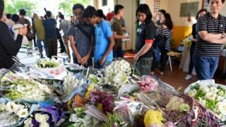 Malaysians look at flowers laid our for victims of an earthquake last week