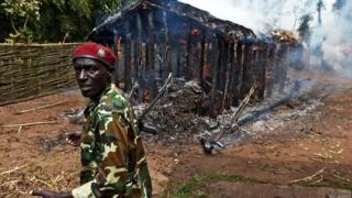 A soldier stands in front of a house set afire by protestors opposed to the Burundian president's bid to stand for a third term in Butagazwa, Mugongomanga, some 30km east of Bujumbura, on 5 June 2015