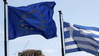 A Greek and a European Union flag billow in the wind as the ruins of the fifth century BC Parthenon temple are seen in the background on the Acropolis