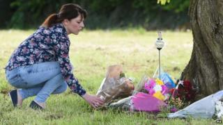Woman leaves flowers as tribute for Amber Peat