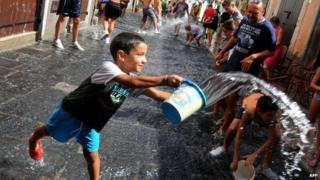 An Italian boy throwing a bucket of water