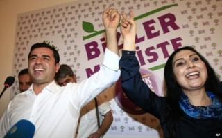 Selahattin Demirtas, left, co-chair of the pro-Kurdish Peoples' Democratic Party, (HDP) and Figen Yuksekdag, the other co-chair celebrate following a news conference in Istanbul, Turkey, 7 June 2015