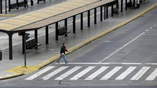 A pedestrian crosses an empty street during a 24-hour nationwide general strike