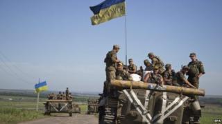 Ukrainian servicemen ride on an armoured military vehicle
