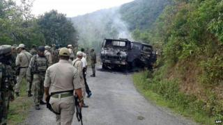 """In this photograph taken on June 4, 2015, Indian security personnel stand alongside the smouldering vehicle wreckage at the scene of an attack on a military convoy in a remote area of Chandel district, about 120 kilometres (75 miles) southwest of northeastern Manipur""""s state capital Imphal."""