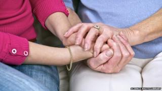 carer and woman hold hands