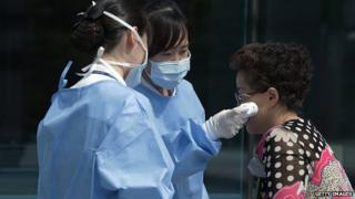 Medical staffs check the temperature of a visitor at Seoul Medical Center