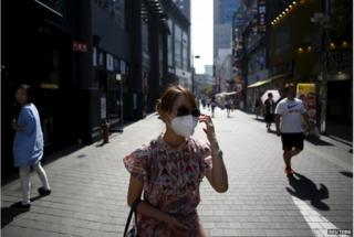 A tourist puts on a face mask to prevent contracting Middle East Respiratory Syndrome (MERS) at Myeongdong shopping district in central Seoul, South Korea, 10 June 2015