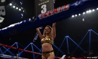 "A ring girl in a gold bikini holding up a ""round 3"" sign"