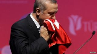 President Erdogan kisses a handmade Turkish flag given to him as a gift at a graduation ceremony in Ankara, Turkey - 11 June 2015