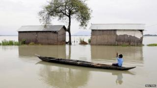 A schoolboy rows his boat past partially submerged huts in the Morigaon district of Assam