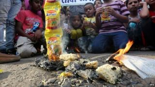 Packets of Maggi brand noodles are set on fire as slum children take part in a protest against them in Bhopal, India, 05 June 2015