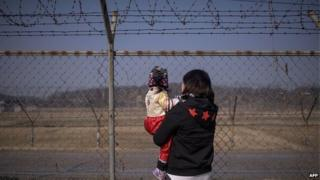 A woman holding a child look towards North Korea as they stand at a military fence at Imjingak park, south of the Military Demarcation Line and Demilitarized Zone (DMZ) separating North and South Korea, on February 19, 2015