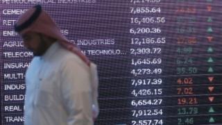 A Saudi investor walks past a screen