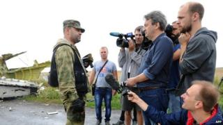 Journalists with Ukrainian rebel officer at site of MH17 disaster - file pic