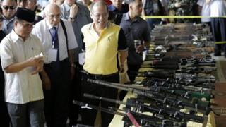 Philippine President Benigno Aquino III (3-L) and Moro Islamic Liberation Front Chairman Al Haj Murad Ebrahim (L) inspect surrendered firearms from the members of rebel group Moro Islamic Liberation Front (MILF) during the first phase of the decommissioning of rebel weapons in the town of Sultan Kudarat, Maguindanao province, Southern Philippines, 16 June 2015.