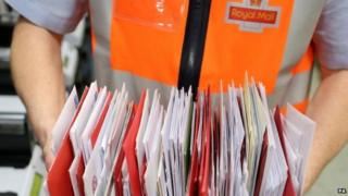 Royal Mail worker holding letters