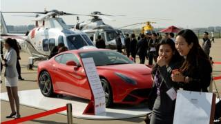 People walk past a Ferrari car and helicopters during the Asian Business Aviation Conference & Exhibition (ABACE2014) at the Shanghai Hongqiao airport in 2014.