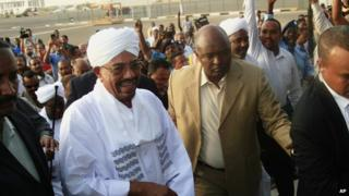 Hundreds of supporters welcome Sudanese President Omar al-Bashir, centre left, on his arrival from South Africa as he walks through the crowd at the airport in Khartoum