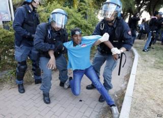 Italian police restrain a migrant on the border with France at Ventimiglia