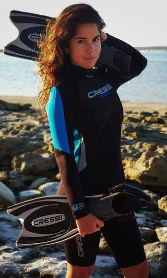 A woman in a wetsuit with the sea in the background