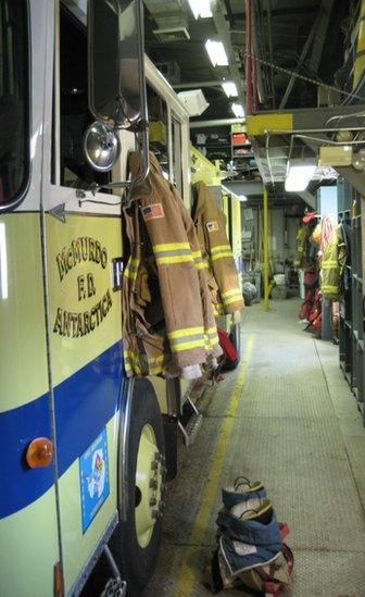 A fire engine reads 'McMurdo F.D. Antarctica'. It is parked in the firehouse, with firefighting gear and equipment stored nearby