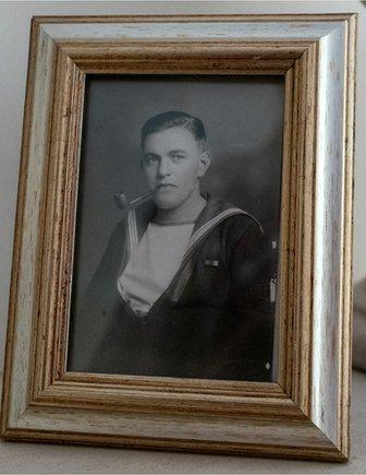A framed photo of Ted in his Navy uniform on his mantelpiece