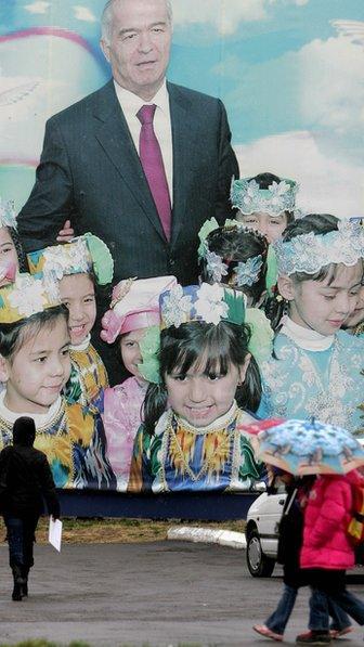 People walk in front of a giant poster of Uzbek President Islam Karimov in Tashkent, 24 December 2007.
