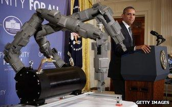 President Obama stands next to a robot