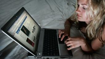 فتاة تجلس أمام الكمبيوتر المحمول