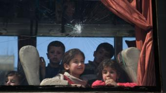 أطفال في حافلة تنقل المدنيين إلى خارج دوما، في الخامس من أبريل/نيسان 2018