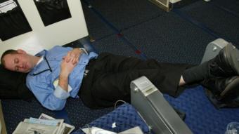 مسافر نائم على أرضية على طائرة
