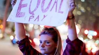 فتاة ترفع لافتة تطالب بالمساواة في الأجور