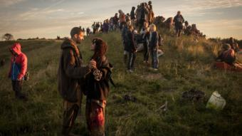 People gather on the ridge overlooking the Avebury Neolithic henge monument, a UNESCO World Heritage site, as they watch the sun rise on June 21, 2018 in Wiltshire, England.