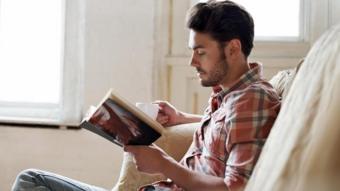 شاب يجلس منفردا ويقرأ في كتاب