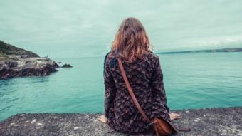 فتاة تجلس بمفردها أمام البحر