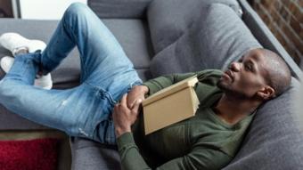 شاب يستلقي على أريكه وفي يده كتاب