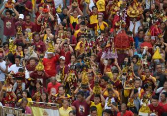 Catholics holds up a replica of the Black Nazarene at a blessing in Manila (7 Jan 2019)