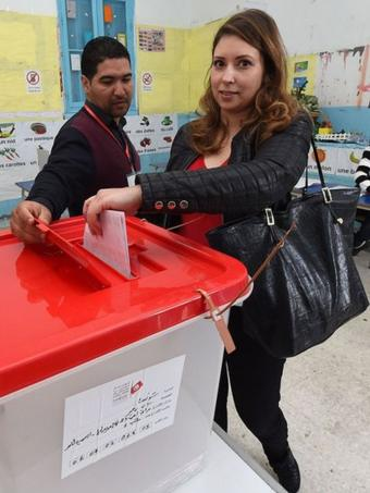 A woman votes in elections in Tunisia.