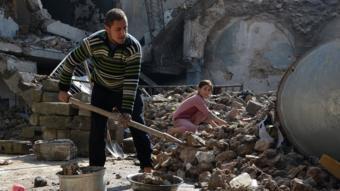 شاب وطفلة يزيلان آثار هدم أحد المباني