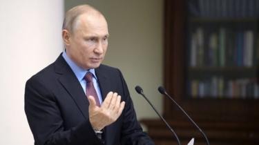 President Putin at a podium delivering the speech on his new passport policy