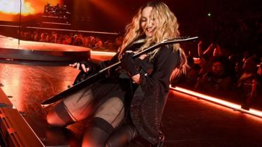 Singer Madonna playing guitar and smiling while on her knees on a stage