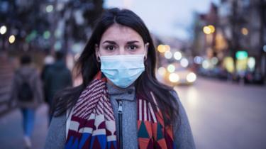 Una mujer con mascarilla en la calle.