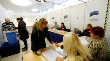An election official inspects a woman's document during the general election at the polling station in Parnu.