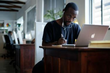 Young black South African sits at a computer