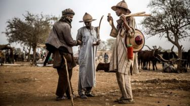 A group of Fulani pastoralist men exchange money after cattle transactions at Illiea Cattle Market, Sokoto State, Nigeria, on April 21, 2019
