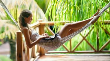 Woman in hammock typing on laptop