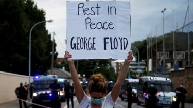 """A woman holds a sign reading """"Rest in peace George Floyd"""" outside the US consulate in Barcelona"""