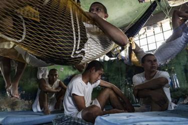 Inmates sit in their cell while others lie in hammocks in Chalatenango Penal Center, El Salvador 7 November , 2018